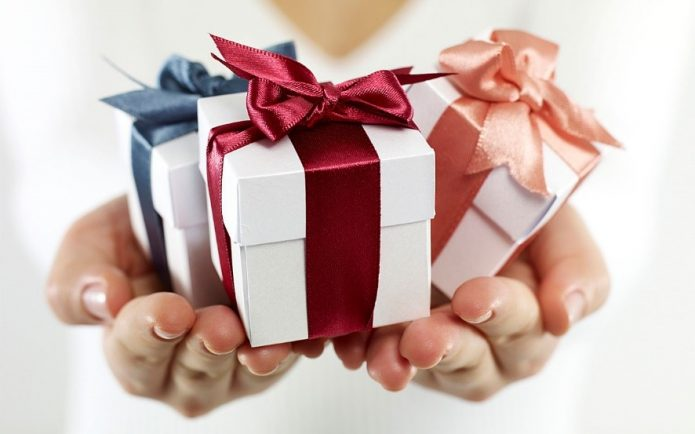 A person giving three small gifts bought from Purple Sunrise