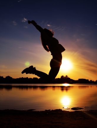 Girl jumping in front of a decorative sunset after finishing a book